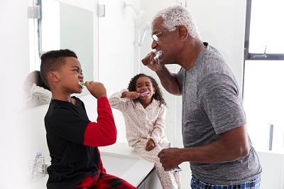 senior african american man teaching grandchildren how to brush teeth at home