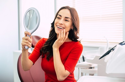 young woman checking out her smile with hand mirror