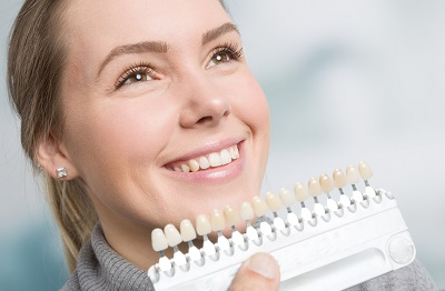 woman matching teeth color for veneer treatment
