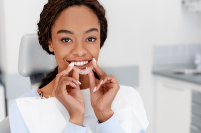 Image of African American woman holding clear braces