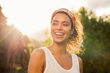 Portrait of beautiful african american woman smiling and looking away at park during sunset
