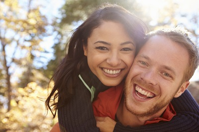 Portrait of mixed race couple smiling in a forest