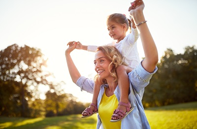 mother giving daughter piggyback ride at the park